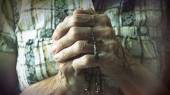 Senior hands holding rosary or crucifix while praying — Stock Photo