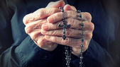 Hands of an elder woman holding a rosary while praying — Stock Photo