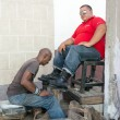 Постер, плакат: Shoe shiner or shoe shine person working