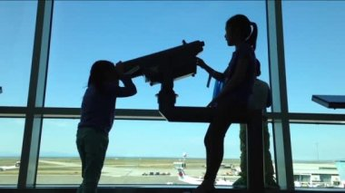 Silhouette of children close up looks through window at planes at airport — Stock Video