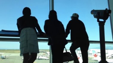 Silhouette of people close up looks through window at planes at airport — Stock Video
