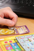 Scratching lottery tickets with computer background. — Stock Photo