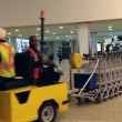 Airport workers moving stacks of luggage carts — Stock Video #55208793