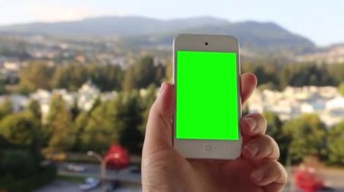Man holds a blank smart phone with a green screen for your own custom content. — Stock Video