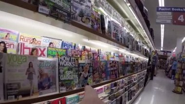 Close up hand choosing guide to ipad magazine at London drugs store — Stock Video