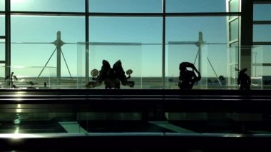 Backlight shot of people on travelator in YVR airport — Stock Video