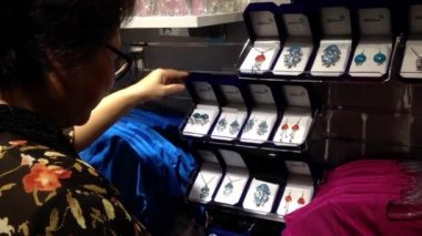 Woman buying earing gift accessory inside gift shop. — Stock Video