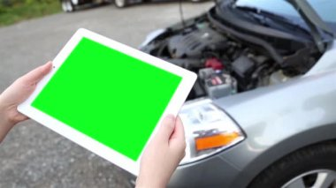 A woman holds a blank tablet PC with a green screen for custom content with luma matte with car background — Stock Video