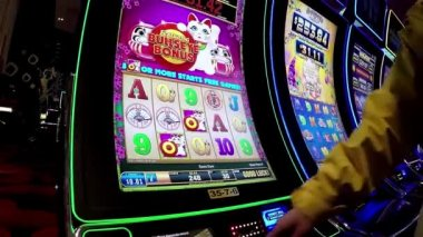 Close up people playing slot machine and pressing cash out button inside Hard Rock Casino in Coquitlam BC Canada with wide angle shot. — Stock Video