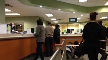 People at a service counter talking to the teller inside TD Bank. — Stock Video