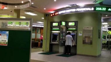 Woman withdraw money at ATM machine inside the TD bank. — Stock Video