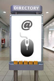 Mouse symbol and direction sign inside shopping mall — Stock Photo