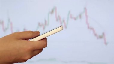 Woman checking mobile phone message with stock market background. — Stockvideo