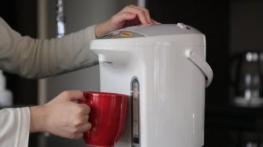 Woman pushing hot water button on electric thermo pot for drinking coffee — Stock Video