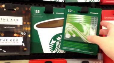 Woman picking starbucks gift card to buy in Coquitlam BC Canada. — Stock Video