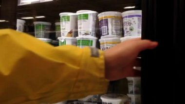 Woman selecting yogurt in grocery store dairy and frozen department. — Stock Video