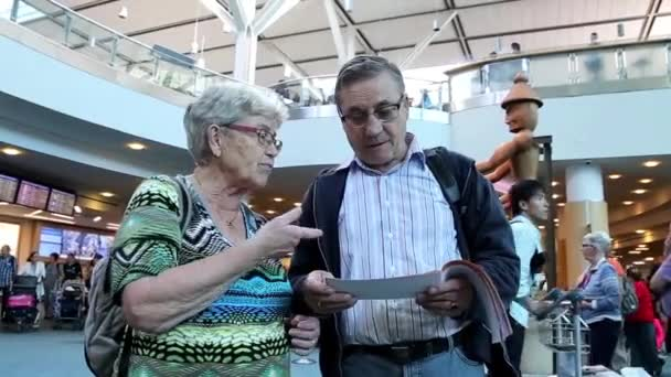Close up of one old couple reading information retrieval at international arrival lobby — Vidéo