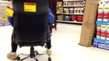 Uomo che cerca la nuova sedia per ufficio all'interno del negozio di droga Londra — Video Stock