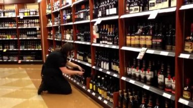 Worker exhibiting wine on the display rack inside BC liquor store — Stock Video