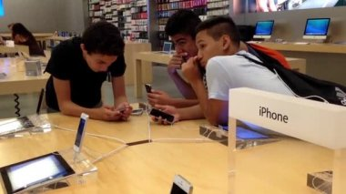 Man typing text message to friend inside Apple store — Stock Video