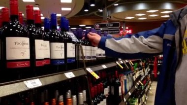 A hand takes bottles of wine from the shelf. — Stock Video