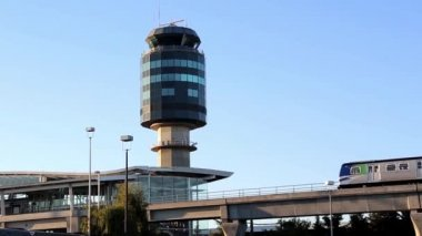 Skytrain commuter rail system at YVR airport station with airport control radar tower background — Video Stock