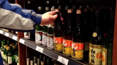 A hand takes bottles of Japanese wine from the shelf — Stock Video
