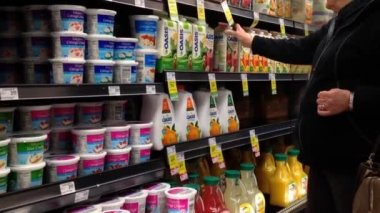 Woman selecting Oasis juice inside supermarket at dairy and forzen department. — Stock Video