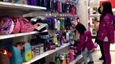 Mother with two children choosing new water bottle inside target store — Stock Video
