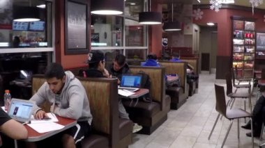 Group of friends sitting at table enjoying meal in Tim hortons with wide angle shot. — Stock Video