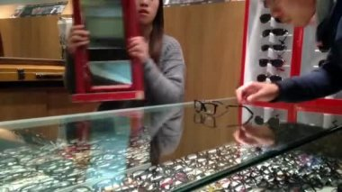 Female optician guides and assists male to choose a new pair of glasses — Video Stock