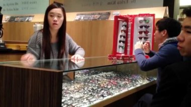 Female optician guides and assists male to choose a new pair of glasses — Stock Video