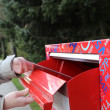 Hand sending a tax report letter in a red mail box — Stock Photo #71674029