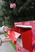 Hand sending a tax report letter in a red mail box — Stock Photo