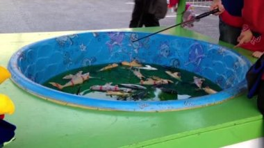 Catching colorful fish float in water game at the West Coast Amusements Carnival — Stock Video