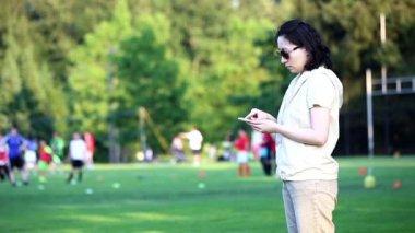 Žena čte mobilní telefon zprávu na pole sport — Stock video