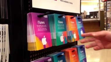 Man picking fifty and twenty five dollar itunes gift card inside supermarket — Stock Video