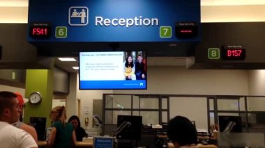 People line up for applying driver license at reception site inside ICBC — Stock Video