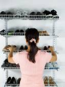 Woman selecting footwear from the shoe rack mounted on wall — Stock Photo