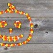 Candy shaped as Halloween Pumpkin on rustic Wood — Stock Photo #54713357