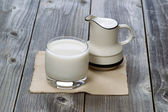 Full Glass of fresh milk and pourer on old wood  — Stock Photo