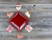 Christmas Cookies decorations around red plate on wood  — Stock Photo
