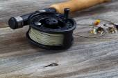Close up of Fly Reel and Flies on Wood  — Photo