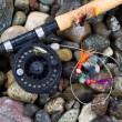 Fly Fishing Pole and Reel with Flies on Wet Stones — Stock Photo #60180187