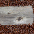 Border of freshly roasted coffee beans on aged wood — Stock Photo #61396585