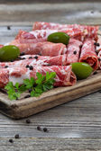Various meats on serving board with rustic background — Stock Photo