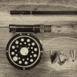 Vintage fly reel and rod on aged wood — Stock Photo #69482379