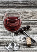 Vintage corkscrew with red wine in glass — Stock fotografie