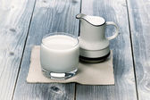 Glass of milk and small pitcher on age wood — Stock Photo