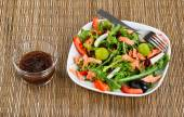 Fresh healthy salad and dressing on natural bamboo place mat — Stock Photo